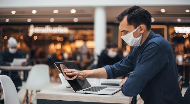 확대 . 방부제로 노트북 화면을 닦는 보호 마스크를 쓴 남자.