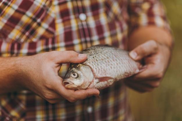 닫기 체크 무늬 셔츠를 입은 남자가 흐릿한 갈색 녹색 배경에 입을 벌린 물고기를 손에 들고 있습니다. 라이프 스타일, 레크리에이션, 어부의 레저 개념. 광고 공간을 복사합니다.