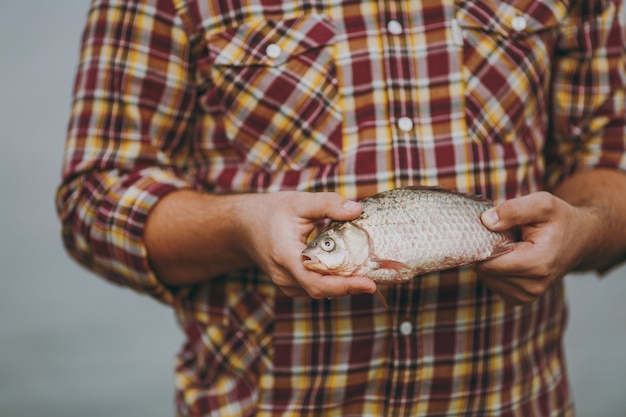 닫기 체크 무늬 셔츠를 입은 남자가 흐릿한 회색 배경에 입을 벌린 물고기를 손에 들고 있습니다. 라이프 스타일, 레크리에이션, 어부의 레저 개념. 광고 공간을 복사합니다.