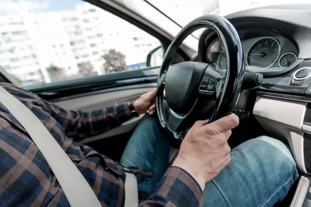 閉じる。一流の車のハンドルの後ろに座っている男。