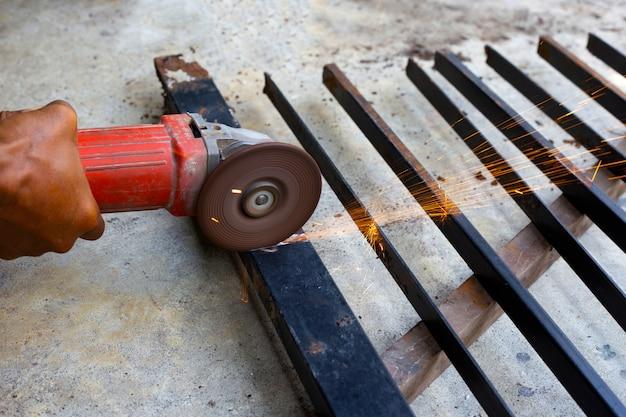 Крупным планом, человек, работающий с угловой шлифовальной машиной. ремонт железных ворот