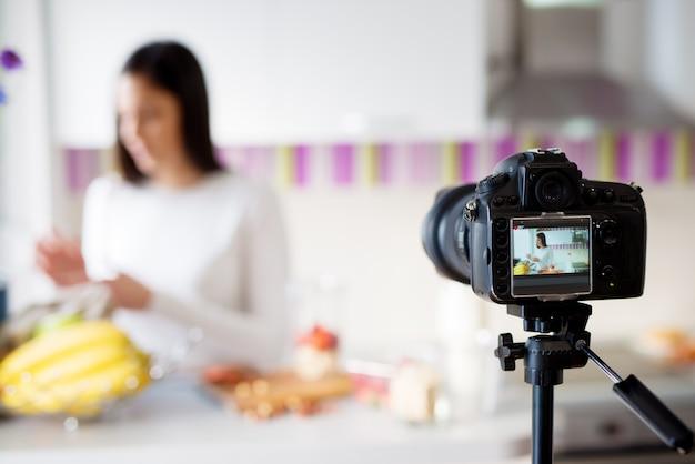 Закройте вверх по изображению камеры фотографируя девушку стоя перед счетчиком действительно яркой кухни.