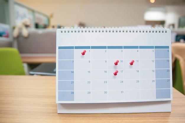 빈 책상 달력에 빨간 핀을 클로즈업.