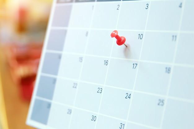 空白の卓上カレンダーの赤いピンをクローズアップします。