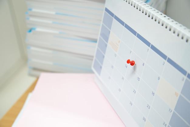 빈 책상 달력에 빨간 핀을 클로즈업합니다.