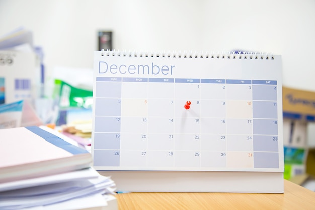 Крупным планом красная булавка на пустой настольный календарь.