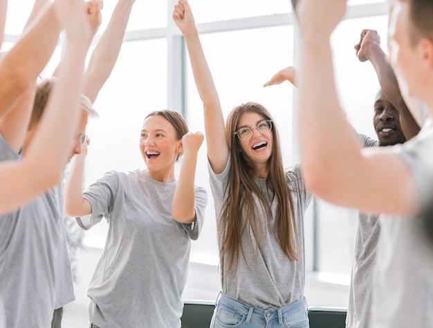 Закройте вверх. команда счастливых молодых людей, демонстрирующих свое единство. бизнес и образование