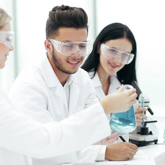 クローズアップ。実験室のテーブルに座っている科学者のチーム。科学と健康