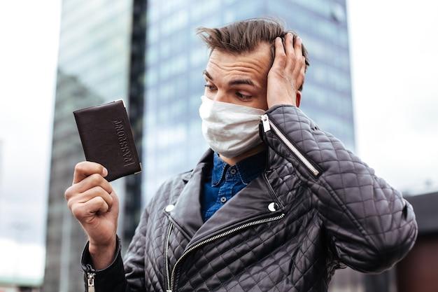 クローズアップ。個人のパスポートを持った保護マスクを身に着けた思いやりのある男。スペースのコピー付きの写真