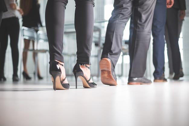 Закройте вверх. через офис бизнес-центра проходят самые разные деловые люди. бизнес фон