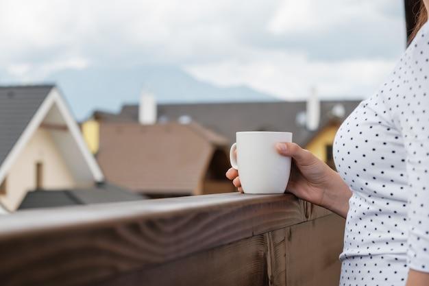 산과 집 지붕이있는 나무 발코니에 여자 손에 흰색 컵을 닫습니다. 휴가의 아침