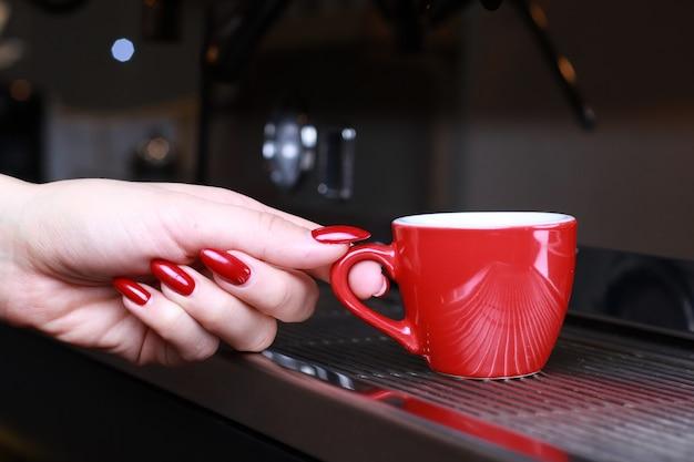 クローズアップ、コーヒーマグカップを持っている女性の手がコーヒーメーカーのグリルに立っています