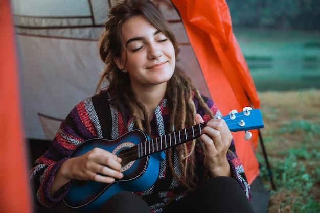 Закройте женщина играть на гитаре после пробуждения