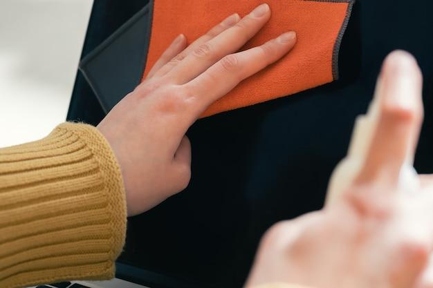 확대. 젊은 여성이 방부제를 사용하여 노트북을 청소합니다