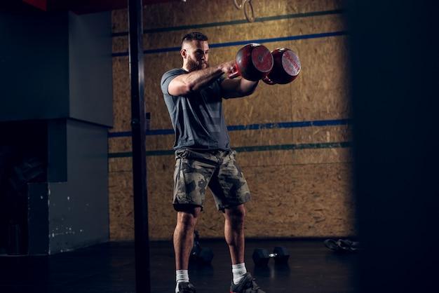暗いジムでトレーニングしながら前に2つの大きな赤いケトルベルを保持している強力なやる気と集中力のある筋肉のひげを生やしたショートヘアボディービルダー男のビューの上にクローズアップ。