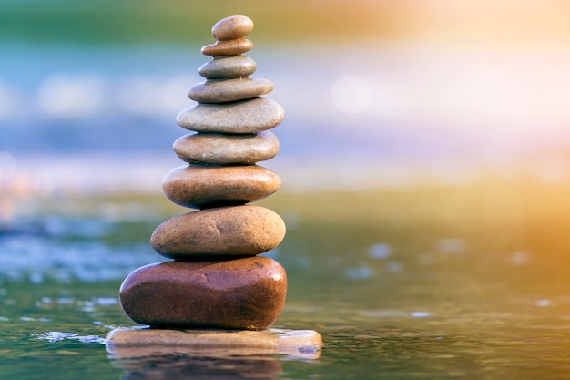 Close-up abstract image of wet rough natural brown uneven different sizes and forms stones balanced like pyramid pile landmark in shallow water on blurred blue-green misty copy space.