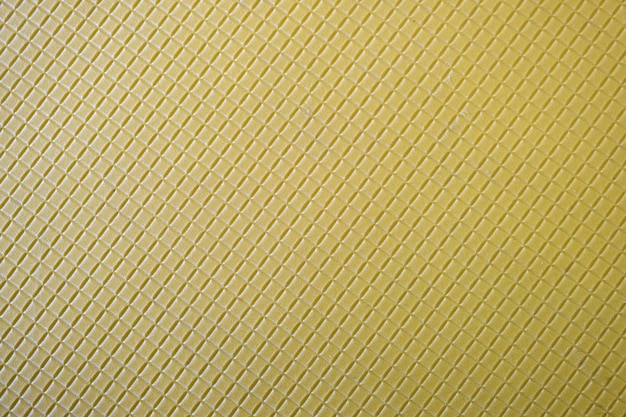 Close up of abstract yellow background with geometric pattern.