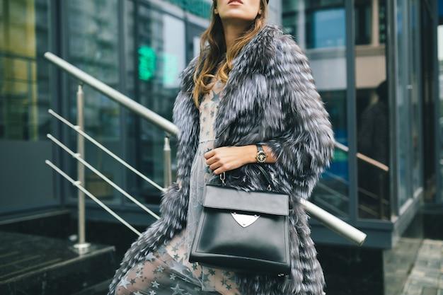 黒革のバッグを保持している暖かい毛皮のコートで街を歩いているスタイリッシュな女性のアクセサリーの詳細をクローズアップ、冬のシーズン、