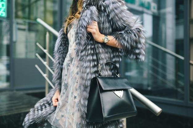暖かい毛皮のコート、冬の季節、寒い天候、革のバッグを持って、ストリートファッションのトレンドで街を歩くスタイリッシュな女性のアクセサリーの詳細を閉じる