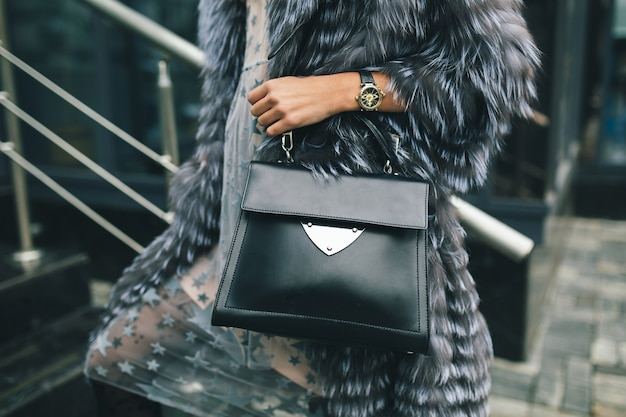 Close up accessories details of stylish woman walking in city in warm fur coat holding black leather bag, winter season,