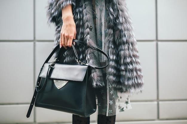 Chiudere i dettagli degli accessori della donna alla moda che cammina in città in caldo cappotto di pelliccia, stagione invernale, clima freddo, tenendo borsa in pelle, tendenza moda di strada