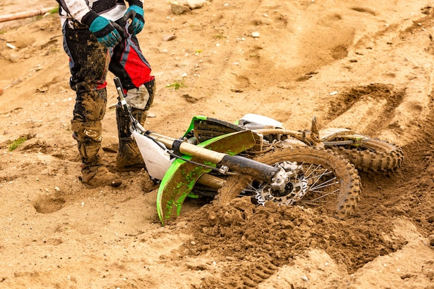Close-up of accident in mountain bikes race in dirt track with flying debris during an acceleration