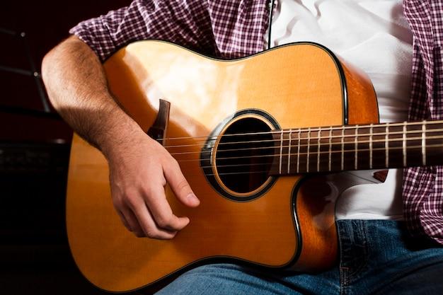 クローズアップアコースティックギターと座っている男