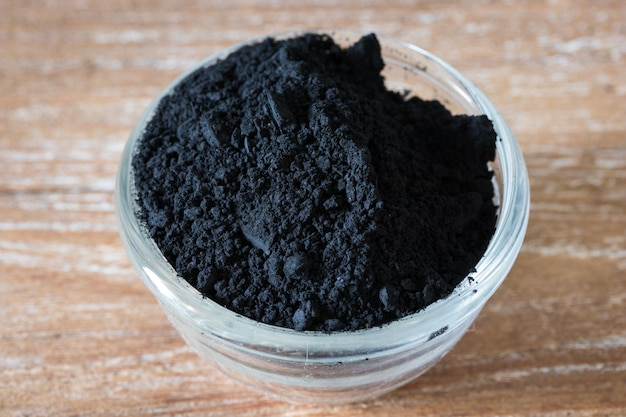 Close up of activated black charcoal powder in a glass bowl on wooden background