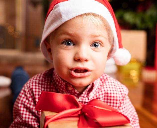 Primo piano del ragazzo adorabile con il cappello della santa e una confezione regalo