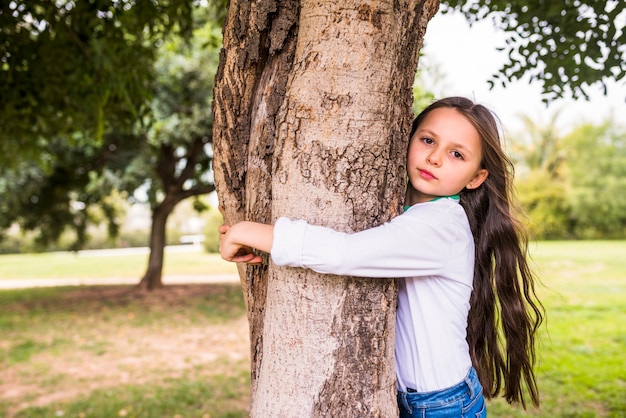 Close-up of a adorable girl hugging tree trunk