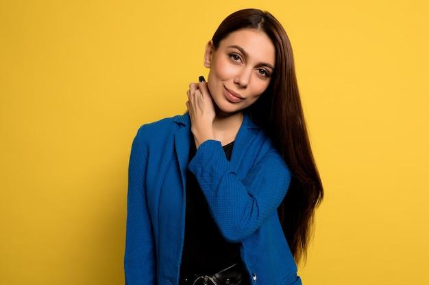 黄色の壁に笑顔でポーズをとって青いジャケットの愛らしい素敵な女性を閉じます。ヨーロッパの女性モデルのポーズ