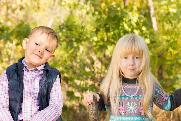 Закройте очаровательных белых маленьких малышей в осеннем модном наряде в парке. снято на фоне зеленых лиственных деревьев.