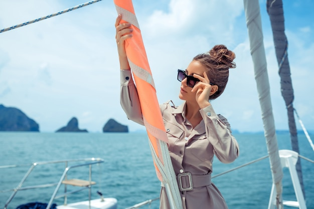 Close up: an adorable young woman in beige dress standing on edge yacht, looking to beautiful nature landscape during trip. happy woman enjoying summer travel. vacation or holiday