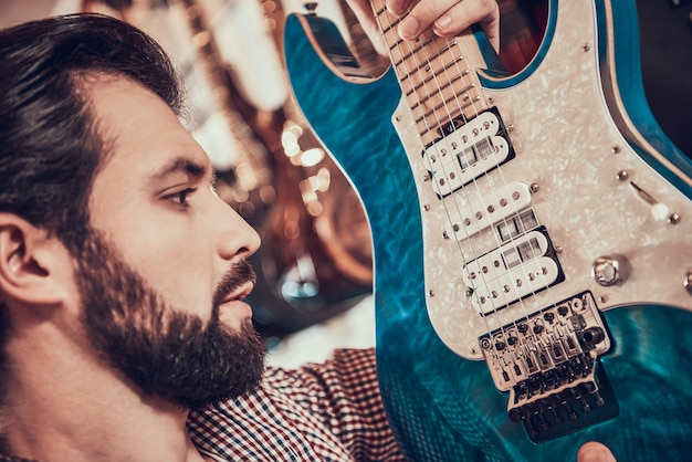 Close up. adult bearded man examines electric guitar closely