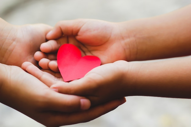 Close up of adult and child hands holding red heart.