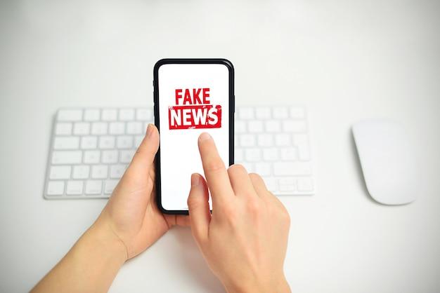 ディスプレイ画面にフェイクニュースのテキストと記号でスマートフォンを持っている大人の手を閉じます。上面図の画像。