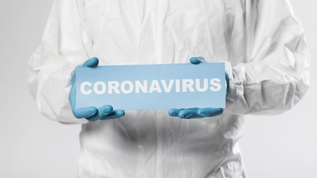 Close-up adult male holding coronavirus sign