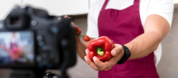 Maschio adulto del primo piano che presenta peperone dolce sulla macchina fotografica