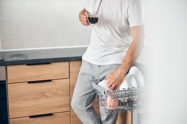 Close up on adult man holding cup in his hand while having rest after doing cleaning around the house