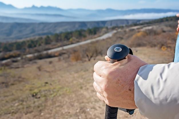 산에서 노르딕 워킹 스틱으로 근접 성인 남자의 손.