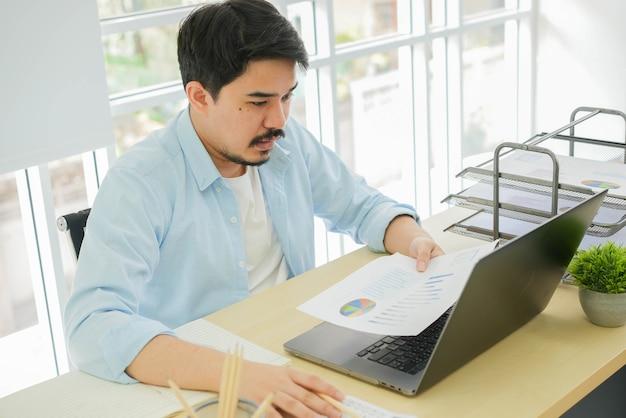 건강한 라이프 스타일 개념에 대한 집에서 작업하는 동안 스트레스 감정으로 회사 이익 통계 보고서를 읽는 성인 중동 남자를 닫습니다