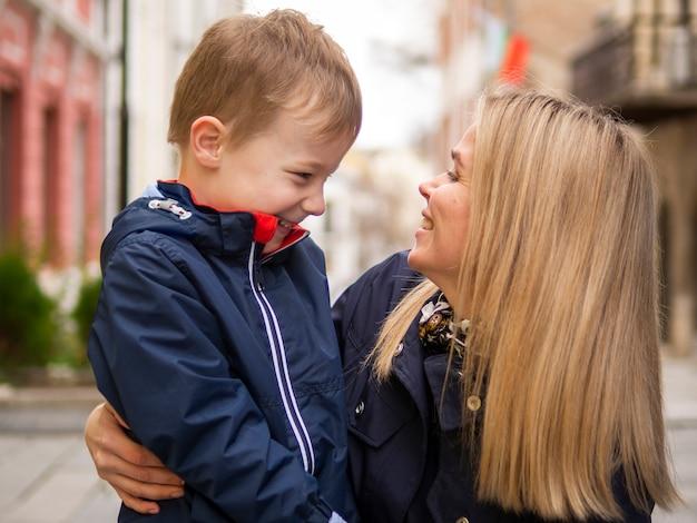 Макро взрослая мама и милый молодой сын играет