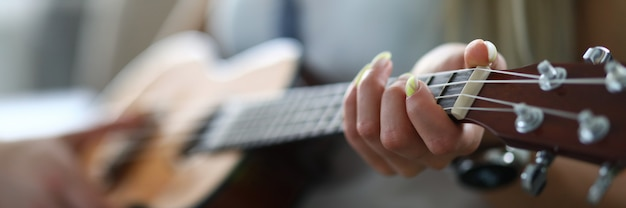Close-up of adult person holding acoustic guitar and playing melody. female hand placed on string. spare time and leisure. talented woman. music and hobby concept