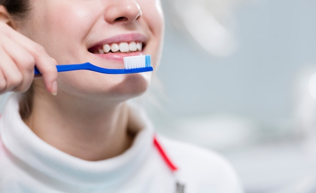 Close-up adult woman brushing teeth