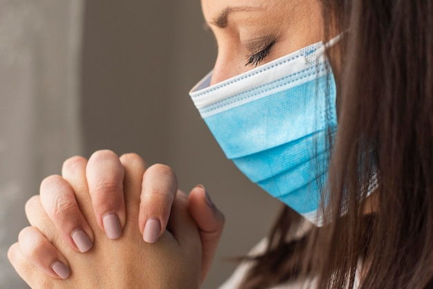 Close-up adult woman with surgical mask praying
