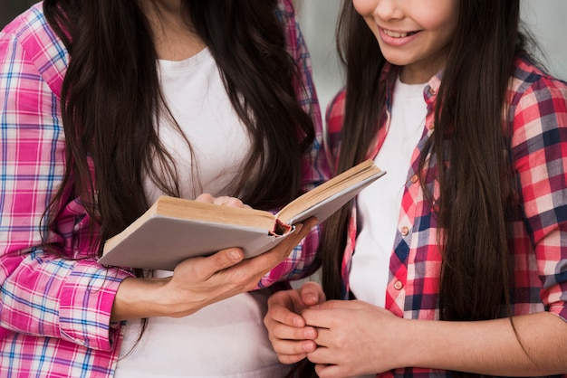 Close-up adult woman and young girl reading a book