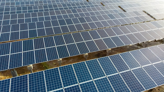 Close up aerial view over solar panels farm (solar cell) with sunlight.
