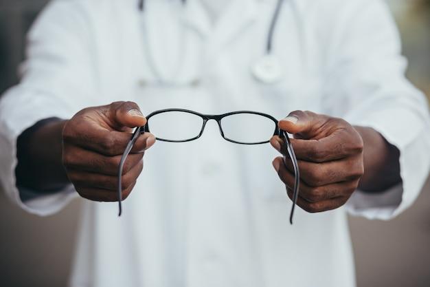 Крупным планом афро-американский врач предлагает очки пациенту, офтальмолог продает очки в магазине