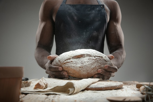Close up of african-american man cooks fresh cereal, bread, bran on wooden table. tasty eating, nutrition, craft product. gluten-free food, healthy lifestyle, organic and safe manufacture. handmade.