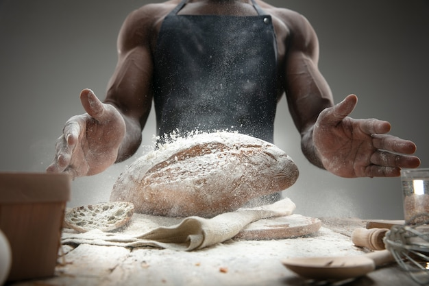 Chiuda in su dell'uomo afro-americano cuochi cereali freschi, pane, crusca sulla tavola di legno. mangiare gustoso, nutrizione, prodotto artigianale. cibo senza glutine, stile di vita sano, produzione biologica e sicura. fatto a mano.